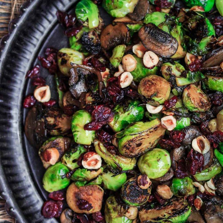 Olive Oil Fried Brussels Sprouts | The Mediterranean Dish. Simple olive oil fried sprouts with mushrooms, cranberries, and hazelnuts, makes a festive vegan and gluten free side dish. See full recipe on TheMediterraneanDish.com #mediterraneanrecipe #friedbrusselssprouts #brusselssprouts #thanskgivingdinner #holidaysidedish #sidedish