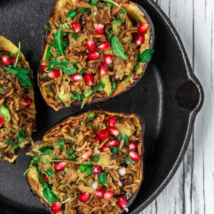 Mediterranean Style Stuffed Acorn Squash Recipe | The Mediterranean Dish.Simple all-start stuffed acorn squash recipe! Prepared Mediterranean-style with an easy rice and lentil pilaf mixture with fresh herbs and pomegranate seeds. A major shortcut makes all the difference! See the recipe on TheMediterraneanDish.com #acornsquash #mediterraneanrecipe #roastedsquash #squashrecipe #thanksigivngdinner