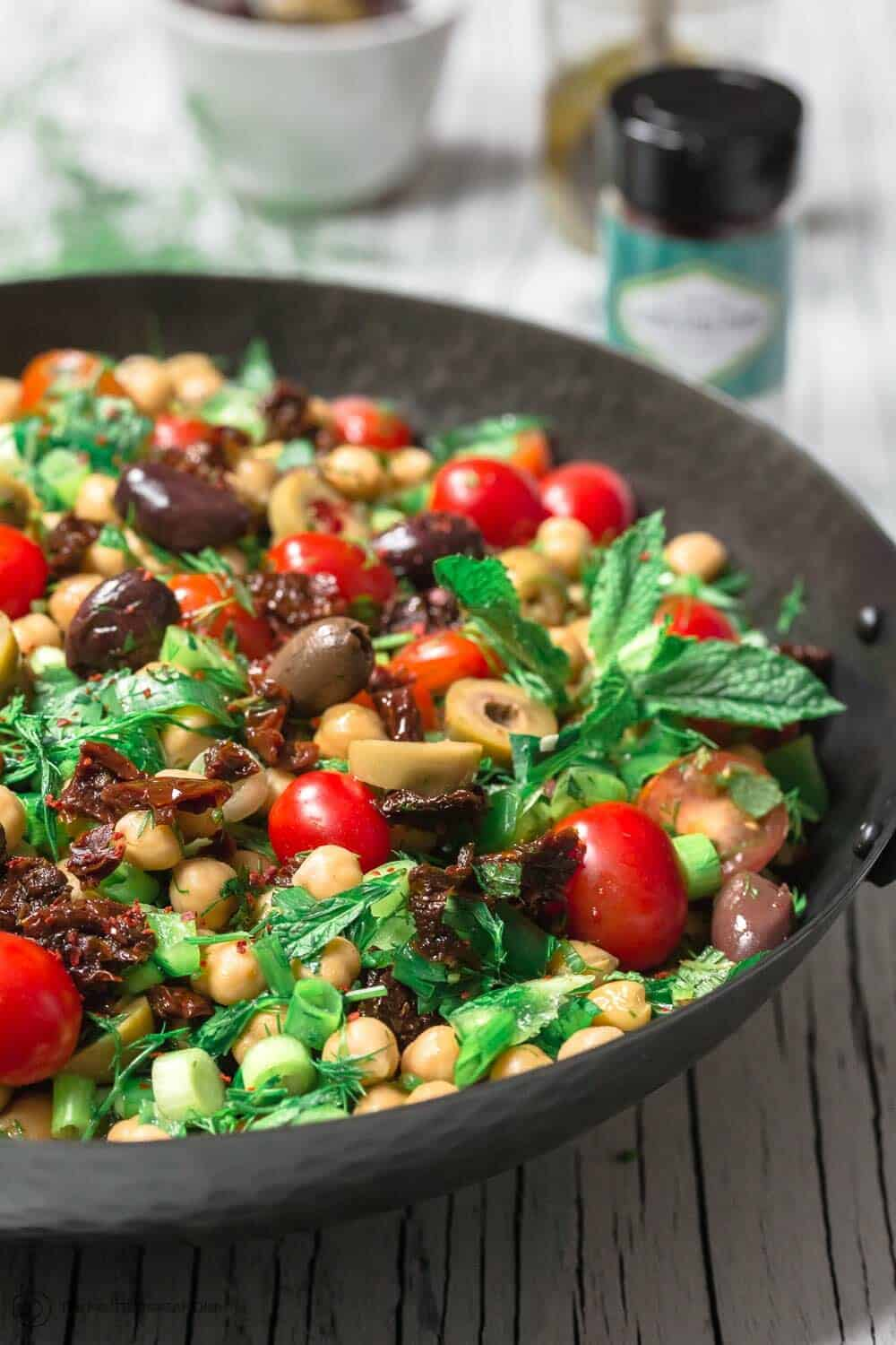 Balela Salad Recipe | The Mediterranean Dish. Bright, flavor-packed Mediterranean chickpea salad with chopped veggies, lots of herbs, and favorites like olives and sun-dried tomatoes. A zesty dressing brings it all together! A simple recipe from TheMediterraneanDish.com #balela #chickpeasalad #mediterraneanfood #mediterraneanrecipe