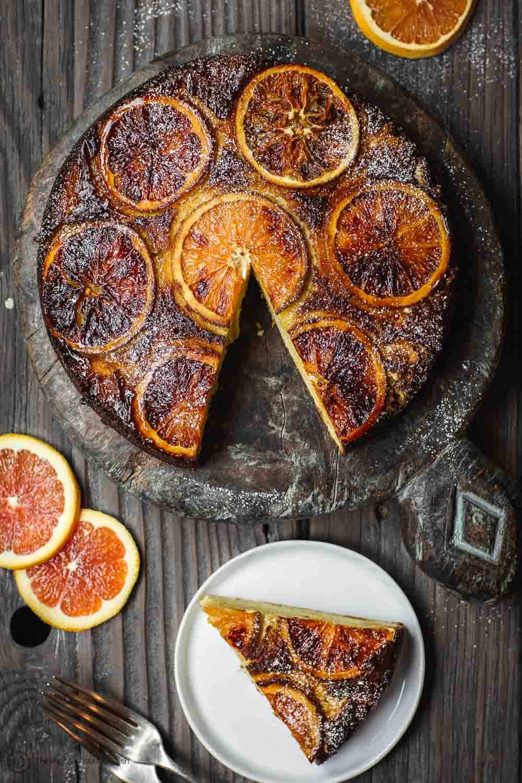One slice of Orange Ricotta Cake served on plate. Cake platter to the side