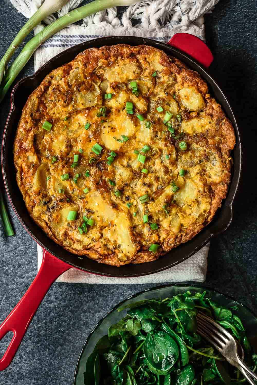 Spanish Tortilla in Skillet served with a Side of Arugula Salad and Spring onions for garnish