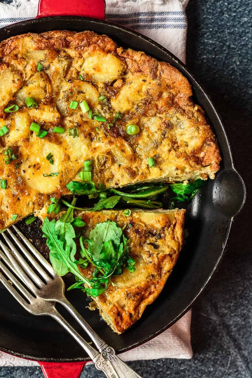 Simple Spanish Tortilla Recipe | The Mediterranean Dish. Spanish tortilla is a simple, satisfying, and perfectly layered potato and egg casserole. Serve it with our easy spinach and arugula salad. Get both recipes on TheMediterraneanDish.com #spanishtortilla #eggcasserole #fritatta #mediterraneanfood #mediterraneanrecipe #brunch #breakfast
