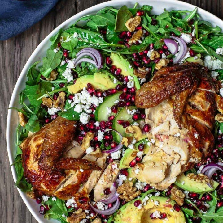 Chicken Arugula Salad with Ginger Pomegranate Dressing | The Mediterranean Dish. Loaded arugula salad with pomegranates, avocado, cucumber, and chicken. The best fresh ginger and pomegranate dressing brings so much flavor and brightness. Simple weeknight dinner! From TheMediterraneanDish.com #arugulasalad #mediterraneandiet #mediterraneanrecipes #mediterraneanfood #healthyrecipes #salad #healthydinner #lowcaloriedinner