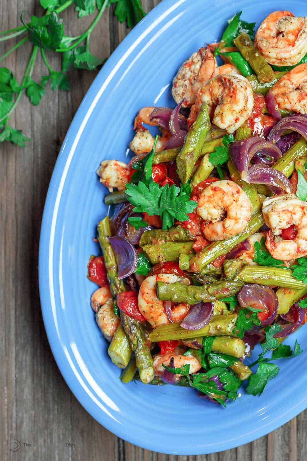 Baked shrimp with Mediterranean flavors and healthy veggies served on a dish