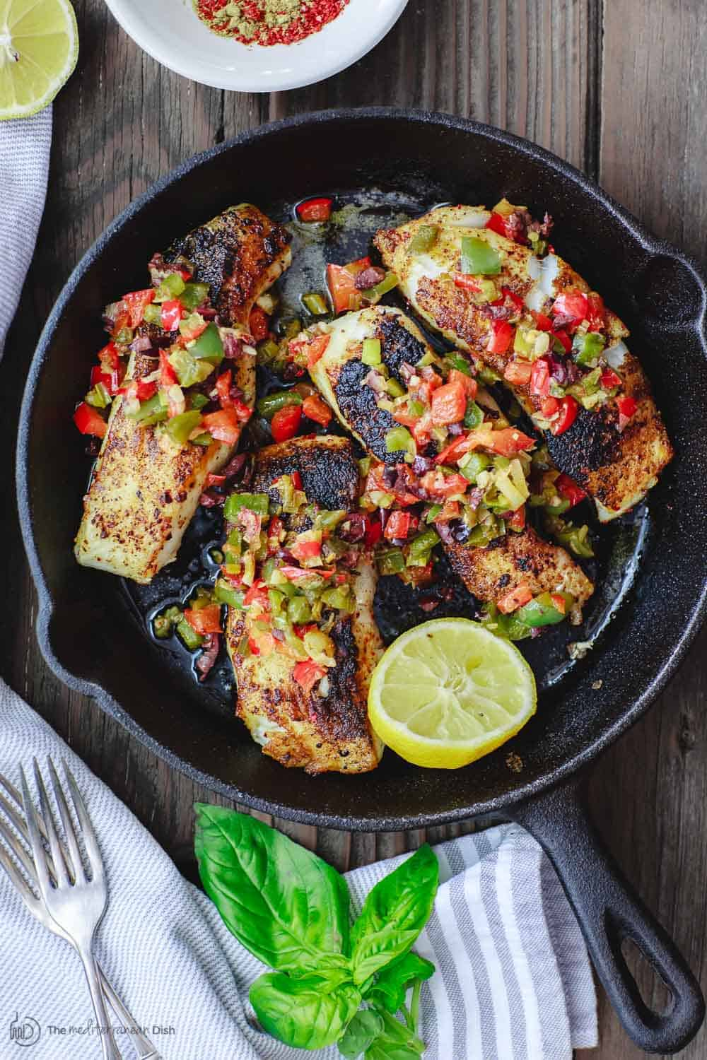 Mediterranean sea bass seared in a skillet with a medley of bell peppers served on top