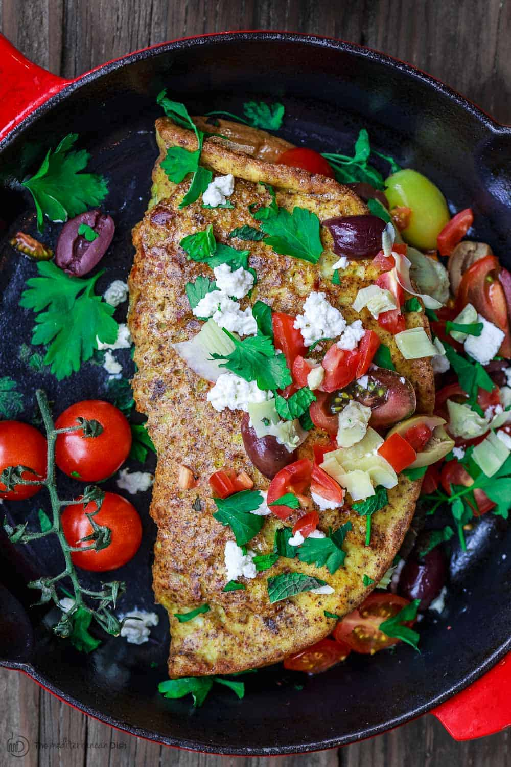 Egg Omelette covered in olives, tomatoes, feta cheese and parsley