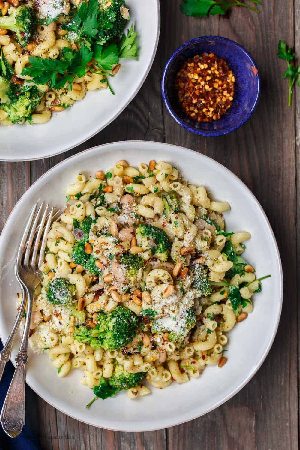 Simple, hearty Mediterranean bean and broccoli pasta. Tossed in olive oil, fresh parsley and favorite spices. A sprinkle of grated Parmesan and some toasted pine nuts seal the deal! See it on TheMediterraneanDish.com #pasta #pastadinner #mediterraneandiet #healthyrecipes #comfortfood #onepotpasta #onepot