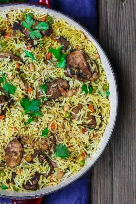 Middle Eastern Chicken and Rice | The Mediterranean Dish. Simple, comforting, one-pot chicken and rice dinner with a tasty Middle Eastern twist. Flavor heaven! Comes together in 30 minutes. Recipe from TheMediterraneanDish.com #mediterraneandiet #middleeasternfood #chickenthighs #onepot #easydinner #healthyrecipes #glutenfree