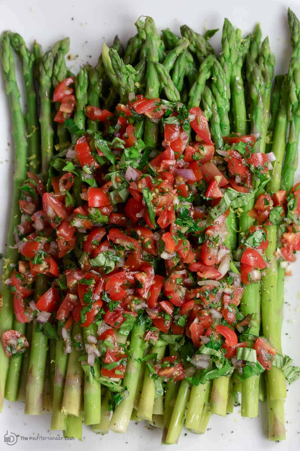 Easy Asparagus Recipe with Mediterranean Salsa | The Mediterranean Dish. Give asparagus a quick blanch, then top with this amazing Mediterranean salsa. Tons of flavor and texture! Serve as an appetizer, side, or Asparagus salad! Recipe from TheMediterraneanDish.com #asparagus #asparagusrecipe #mediterraneandiet #mediterraneanrecipe #mediterranean #mediterraneanfood #glutenfreerecipe #easyrecipe #sidedish #mediterraneansalad #healthyrecipes #veganrecipes