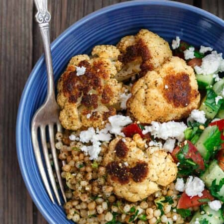 Herbed Couscous Recipe with Roasted Cauliflower | The Mediterranean Dish. Perfectly satisfying dinner bowls with flavor-packed herb couscous, perfectly roasted cauliflower, and an easy Mediterranean salad. Recipe comes with tips for best roasted cauliflower! Omit the feta for vegan dinner bowls. Recipe from TheMediterraneanDish.com