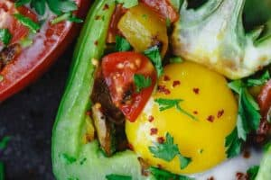 Easy Stuffed Peppers | The Mediterranean Dish. These stuffed peppers are filled with a gluten free and vegetarian potato hash and topped with a perfectly melty egg. Serve them for brunch or dinner, you'll love these healthy stuffed peppers, prepared Mediterranean style. See it on TheMediterraneanDish.com #stuffedpeppers #mediterraneandiet #breakfast #brunch #potatoes #potatohash #glutenfree #breakfasthash #easyrecipes #bellpeppers #healthyrecipe #vegetarian #mothersdaybrunch