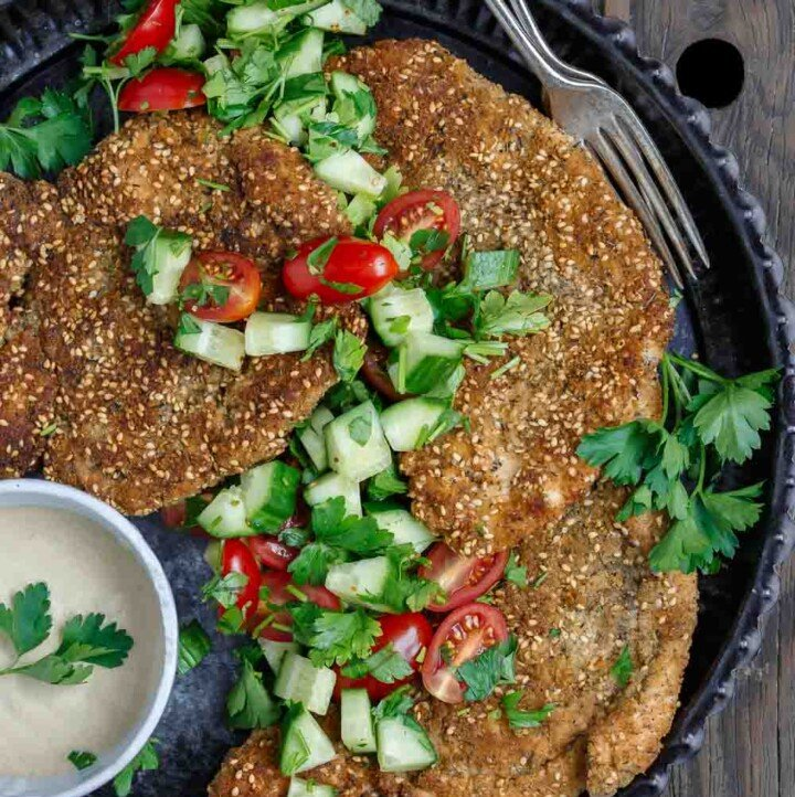 Za'atar Breaded Chicken Recipe | The Mediterranean Dish. Best breaded chicken you'll ever have! Chicken cutlets are prepared to tender perfection and given a golden, perfectly crispy breading with za'atar and toasted sesame seed. See our suggestions for sides and salads. Recipe from TheMediterraneanDish.com #chickenrecipes #breadedchicken #chickendinner #mediterraneanfood #30minutemeal #chicken