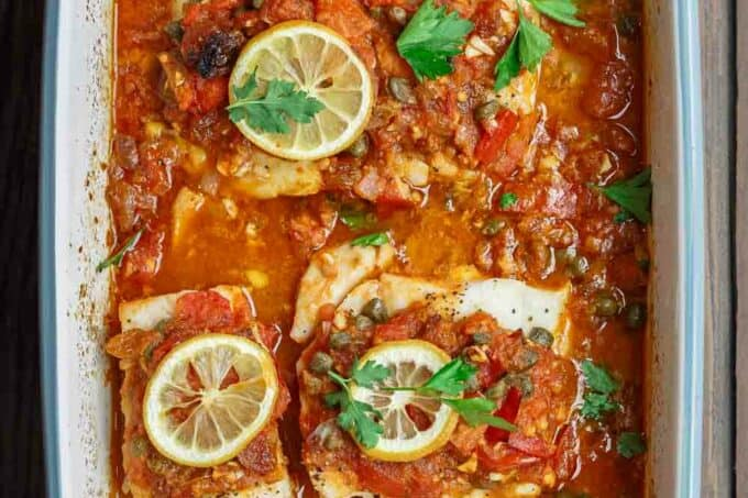 Mediterranean Baked Fish Recipe with Tomatoes and Capers | The Mediterranean Dish. Easy, bright, flavor-packed baked fish, prepared Mediterranean style with spices, tomatoes and capers. From TheMediterraneanDish.com #healthyrecipes #fishrecipe #bakedfish #cod #halibut #glutenfree #seafoodrecipe #seafood #fish #mediterraneandiet #mediterranean #easyrecipe