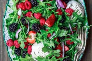 Burrata Arugula Berry Salad | The Mediterranean Dish. This berry salad recipe is a must-try! The perfect summer salad with loads of berries, peppery arugula, and burrata cheese. A light citrus and olive oil dressing is all you need!
