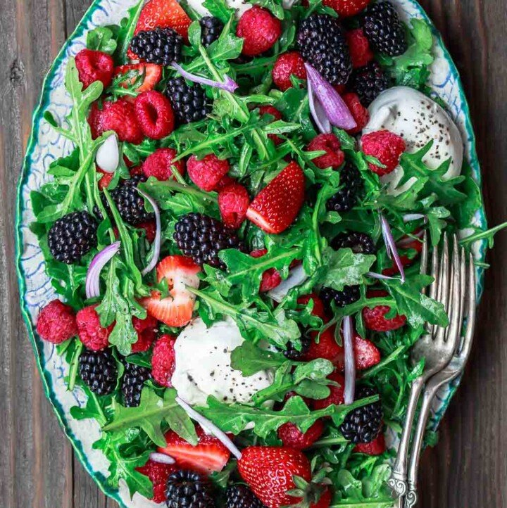 Arugula salad with burrata cheese, raspberries, strawberries and blackberries served in a large plate