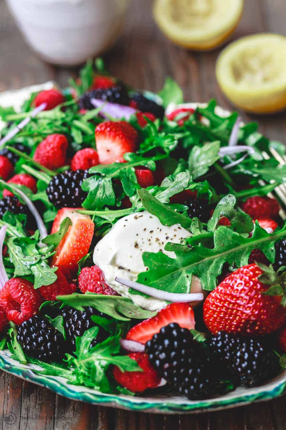 Burrata Arugula Berry Salad | The Mediterranean Dish. This summer berry salad will rock your world. Loads of strawberries, blackberries, and raspberries with peppery arugula and creamy burrata cheese. And the light citrus olive oil dressing is perfect here!