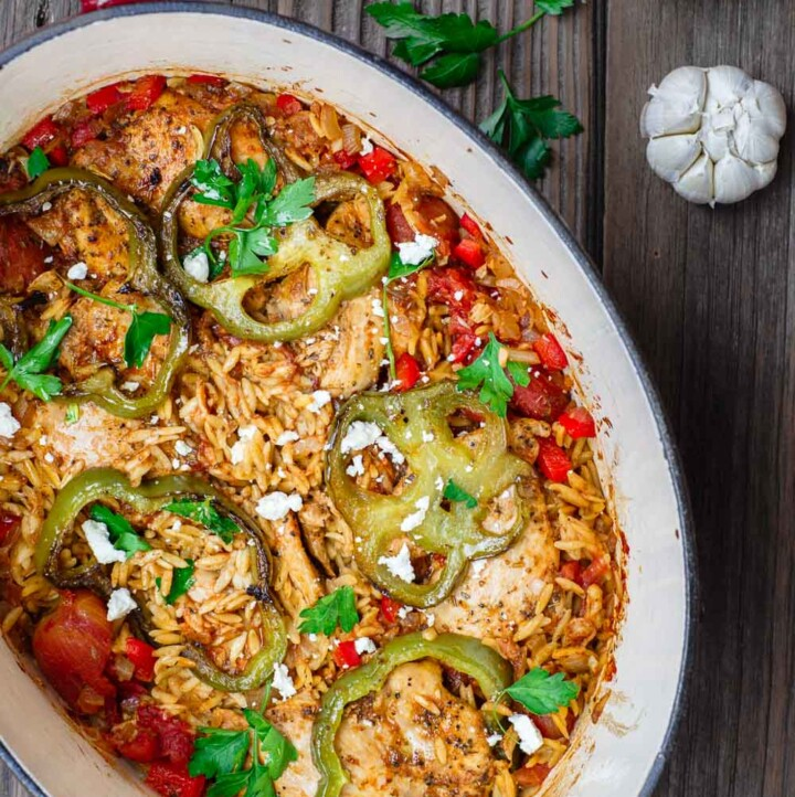 Greek Baked Chicken Orzo Recipe | The Mediterranean Dish. The perfect one-pot chicken and orzo dinner. Perfectly seasoned chicken, nestled into a mixture of tiny orzo pasta with onions, bell peppers, and tomato. This is a dinner for any night of the week. Easy, and absolutely satisfying. From themediterraneandish.com #greekfood #mediterraneanfood #mediterraneandiet #chickendinner #chickenrecipe #healthyrecipe #onepotdinner #easydinner