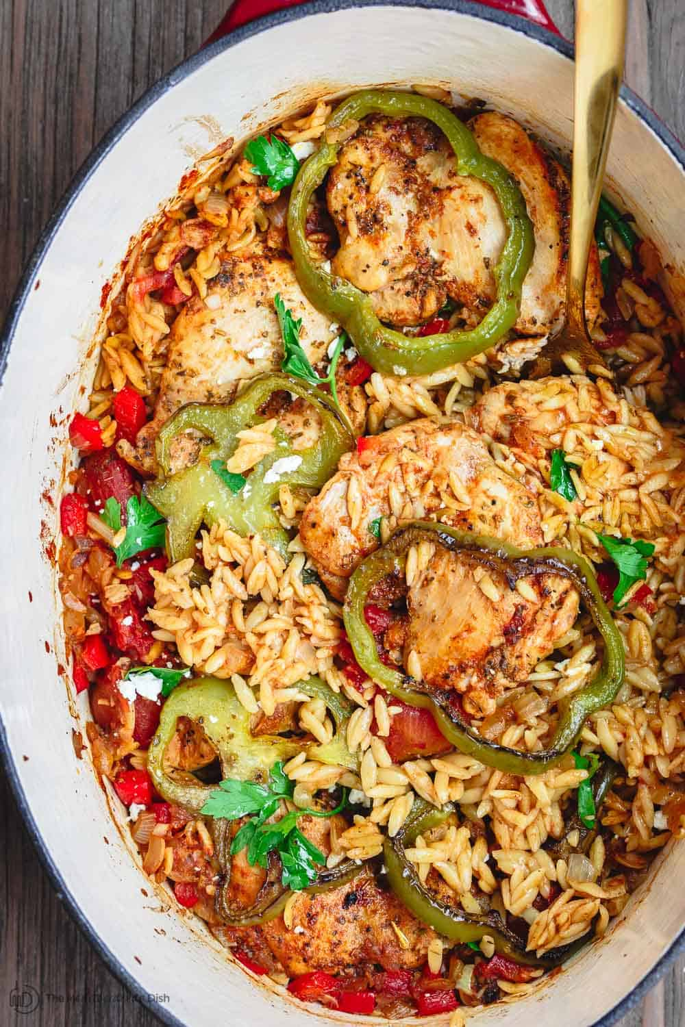 Greek Baked Chicken Orzo Recipe | The Mediterranean Dish. This is the perfect weeknight dinner! One-pot Greek chicken with orzo, onions, bell peppers, and tomato. And loads of Greek flavors. From themediterraneandish.com #greekfood #mediterraneanfood #mediterraneandiet #chickendinner #chickenrecipe #healthyrecipe #onepotdinner #easydinner
