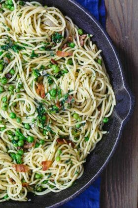 Simple Pasta with Peas and Pancetta | The Mediterranean Dish. Super bright and flavor-packed pasta. Pasta with peas in a light garlic and olive oil sauce. Pancetta or bacon, fresh herbs, and lemon zest add a lot of flavor. Recipe from TheMediterraneanDish.com #pasta #pastarecipe #spaghetti #peas #mediterraneandiet #mediterraneanrecipes #Italian #Italianfood #Italianrecipes #springrecipe #pastarecipe #oliveoilrecipe