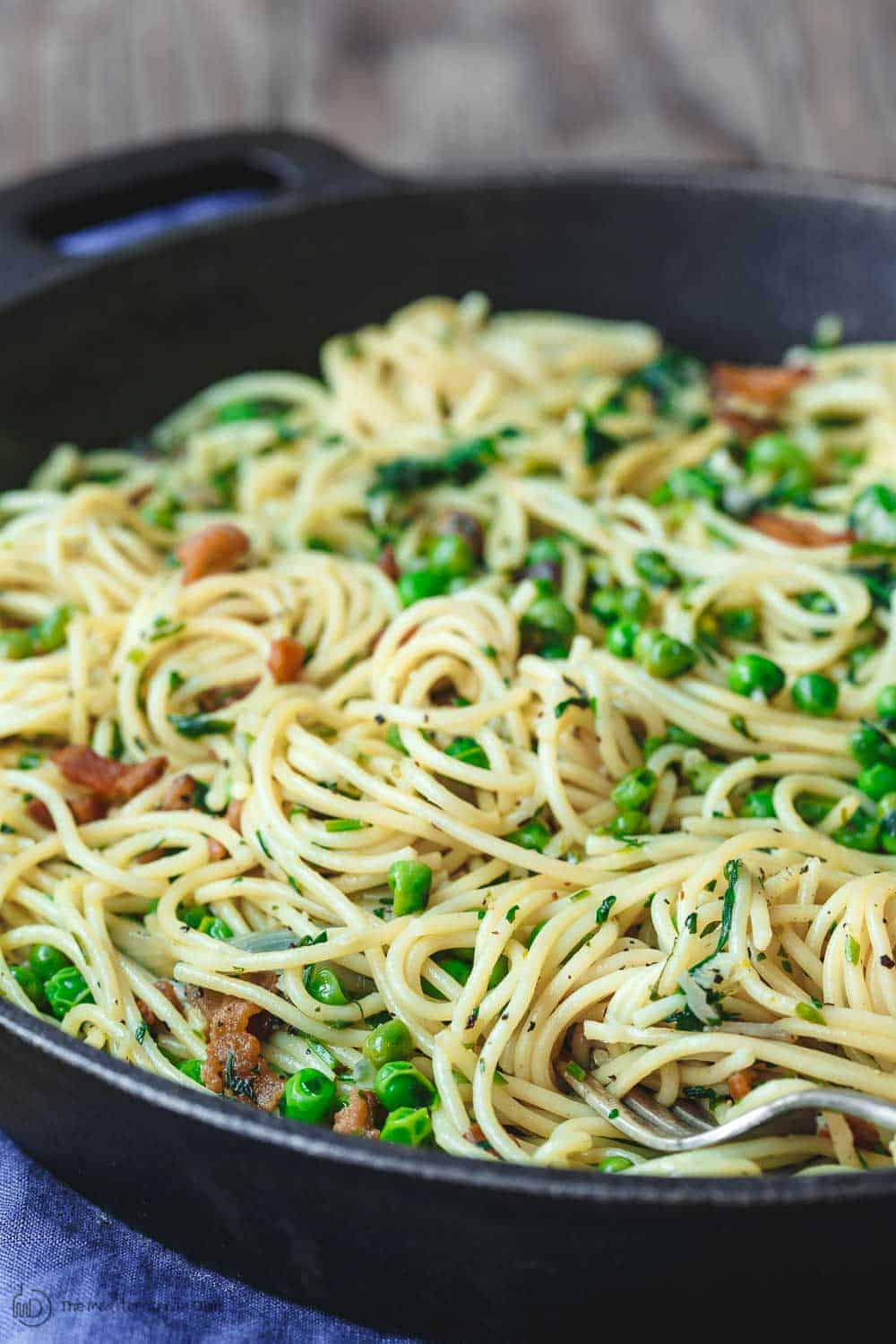 Close-up of peas and pancetta served on pasta