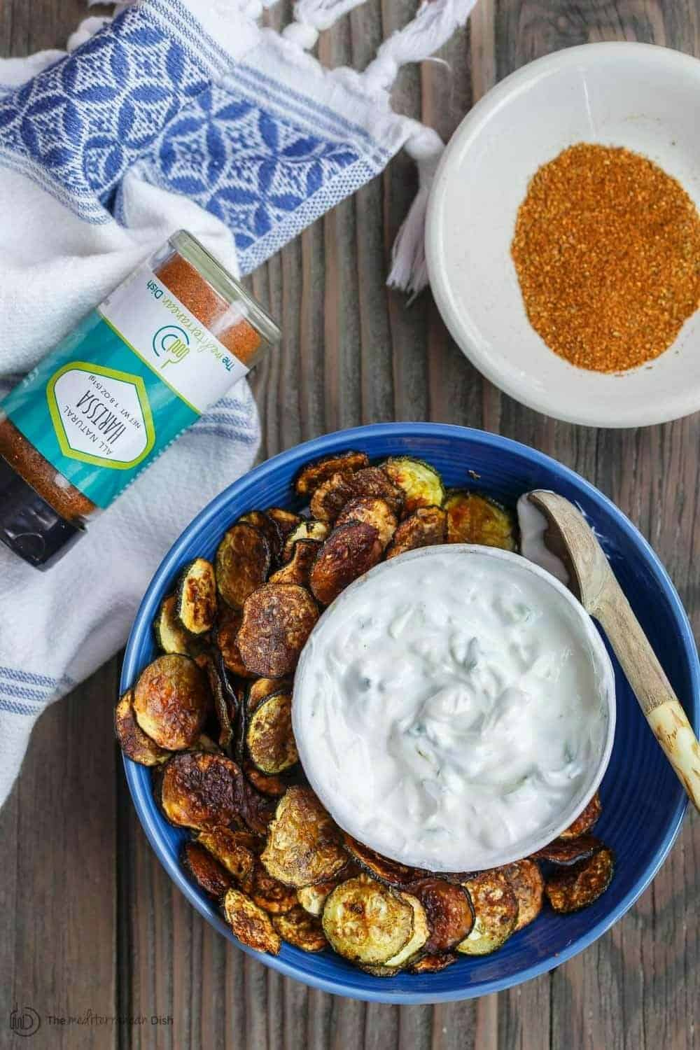 Zucchini Chips with a bowl of Harissa spice blend served on the side with Greek Tzatziki Dip
