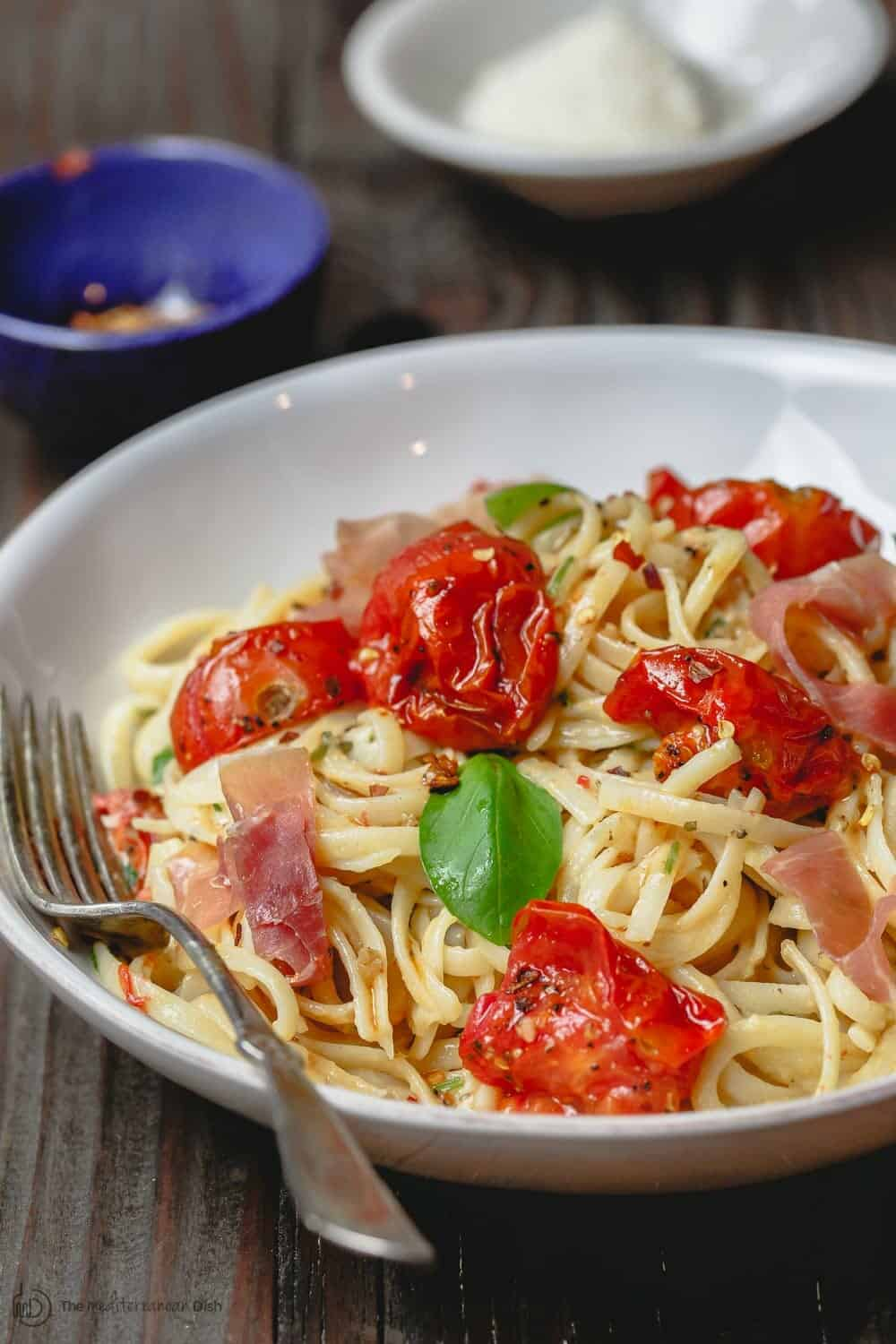 Carbonara Recipe with Roasted Tomatoes | The Mediterranean Dish. A lighter, and flavor-packed cabornara recipes with garlic roasted tomatoes and fresh herbs. You can add ribbons of prosciutto, if you like. A couple of tricks make a perfectly creamy carbonara. Recipe from themediterraneandish.com #pasta #pastarecipe #italianfood #mediterraneandiet #carbonara #easyrecipe