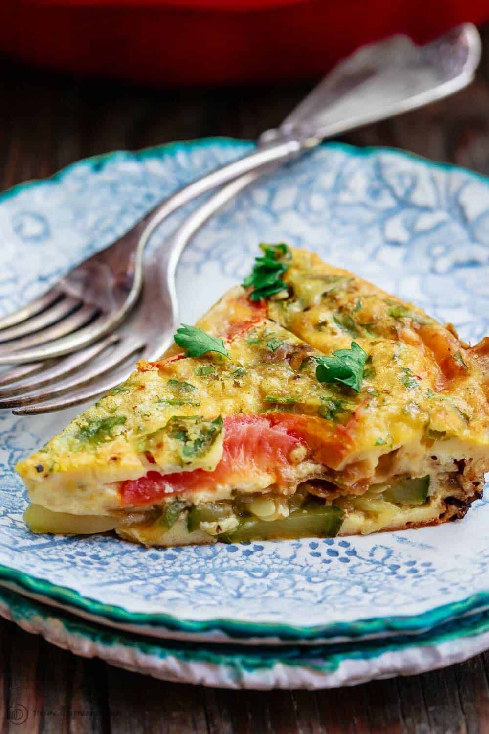 Crustless Zucchini Quiche Recipe | The Mediterranean Dish. Simple crustless zucchini quiche recipe with fresh herbs, tomatoes, and shallots. Perfect for breakfast, lunch, or a light dinner. See our suggestions for what to serve along. #zucchini #quiche #crustlessquiche #zucchinirecipe #breakfast #brunch #holidaybrunch #vegetarianrecipes #savorypie #eggs #mediterraneandiet #mediterraneanrecipes