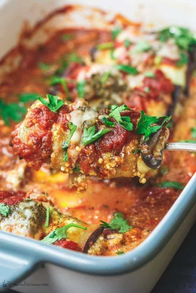 one eggplant rollatini being scooped up from the casserole dish