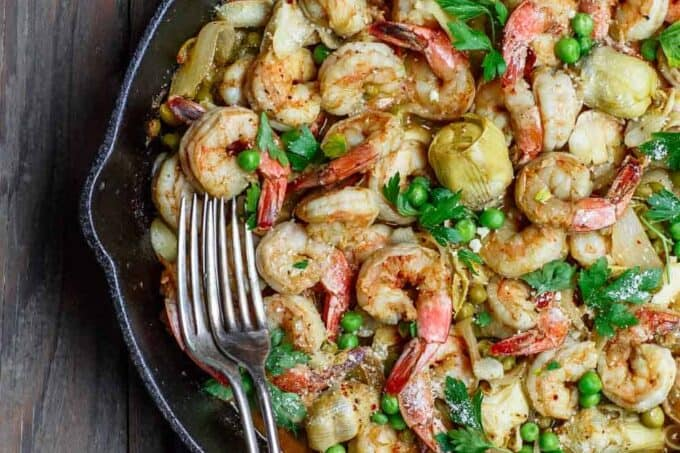 Easy garlic shrimp recipe with peas and artichokes! A quick and bright one-skillet meal. Be sure to see our suggestions for what to serve along. Recipe from TheMediterraneanDish.com #shrimp #glutenfree #mediterraneandiet