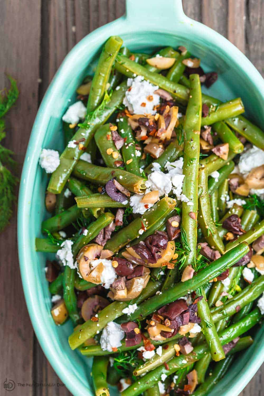 Greek Green Bean Salad Recipe | The Mediterranean Dish. Perfectly tender, flavor-packed green bean salad prepared Greek style. A garlicy, zesty dressing pulls it together, and a sprinkle of feta and chopped marinated olives take it to a new level of delicious. Get the easy recipe on themediterraneandish.com #greenbeans #greekfood #greekrecipe #mediterraneanrecipe #mediterraneandiet
