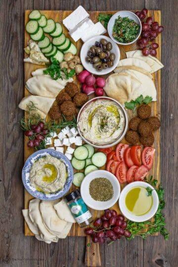 Mediterranean breakfast board with falfel, hummus, baba ganoush, fresh sliced vegetables and olives