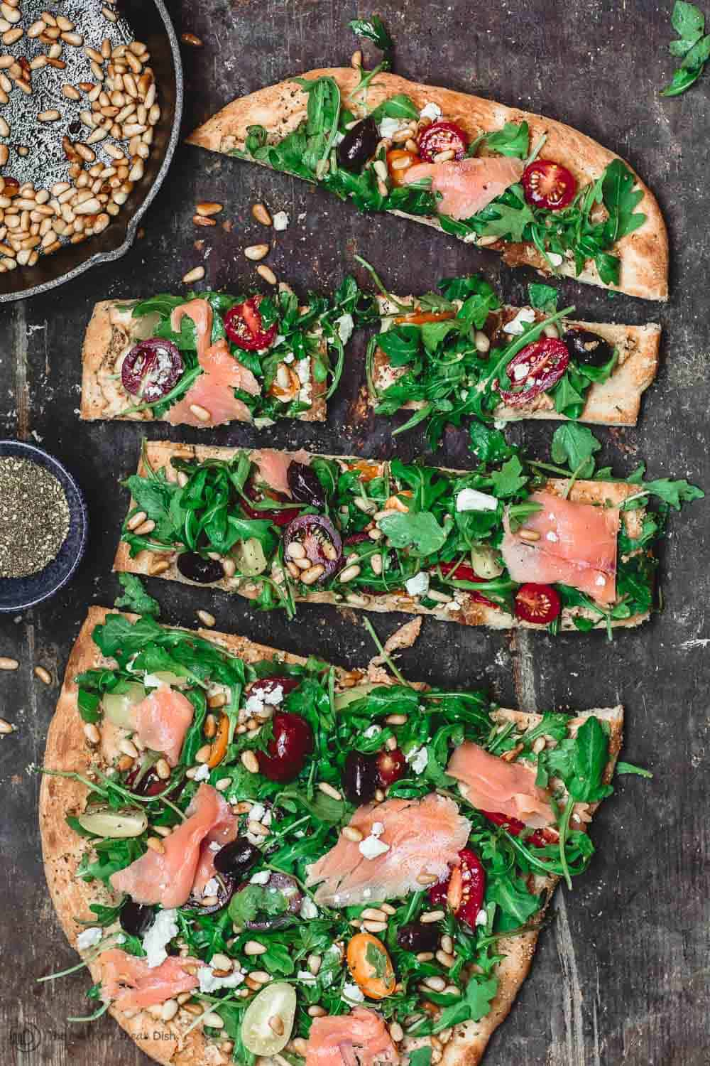 Sliced Flatbread with arugula and smoked salmon to serve as appetizer