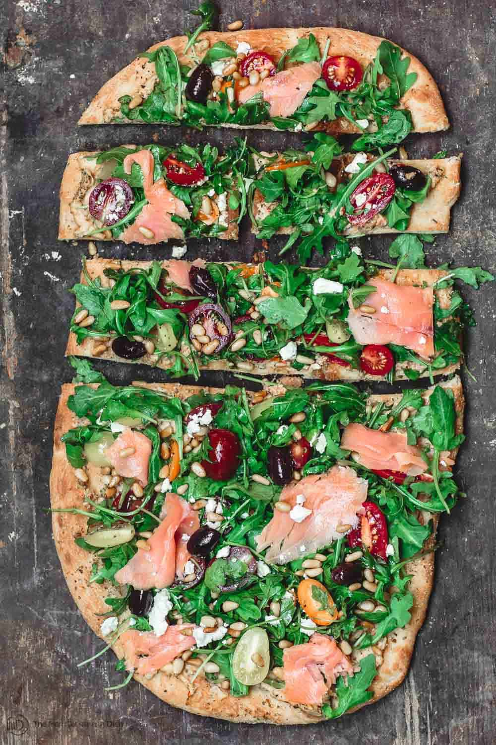 Flatbread with hummus, arugula, tomatoes, smoked salmon and more. Sliced in small pieces to serve as appetizer