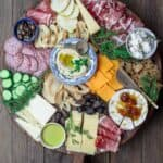 Best Cheese Board with assorted cheeses, cured meats, olives, cucumbers, and dried fruits