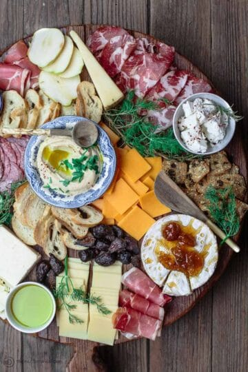 To make the best cheese board, you need a variety of four cheeses, meats, and accompaniments