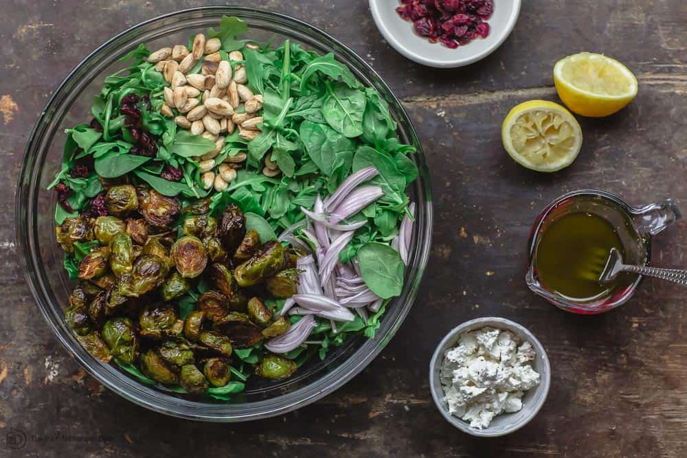 Large mixing bowl containing brussel sprouts, spinach, arugula, shallots, and almonds. A small bowl of feta cheese and a small bowl of cranberries on the side. Vinaigrette ready to be pourd