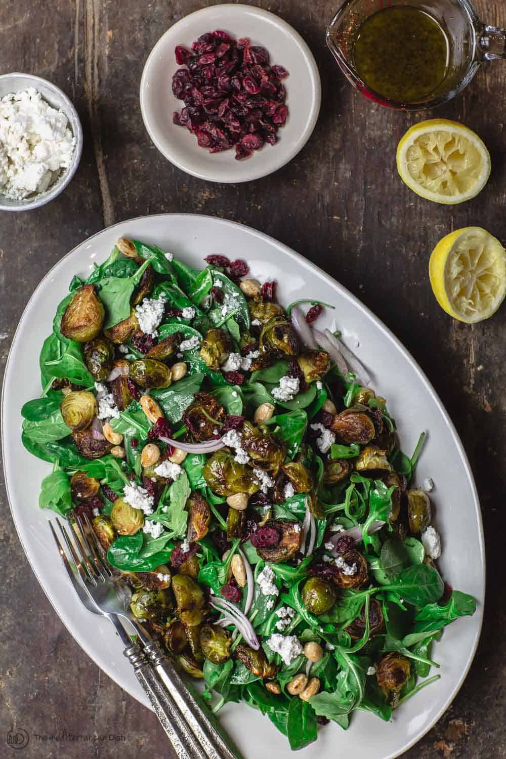 Mediterranean roasted brussels sprouts salad with spinach, arugula, cranberries, almonds and feta. Presented on serving platter with more cranberries and feta cheese on the side.