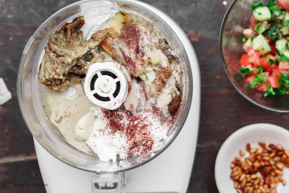 Cooked eggplant in food processor with tahini, yogurt, garlic, and lemon juice to make baba ganoush dip