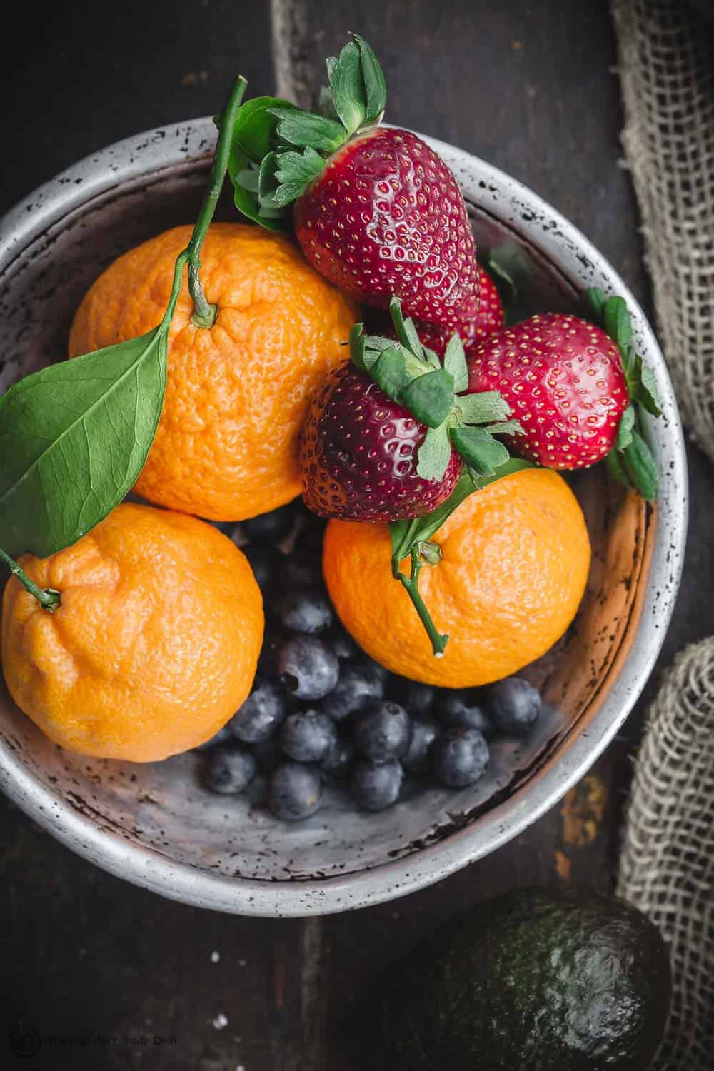 Fresh fruits including citrus fruit and berries in a bowl for a Mediterranean diet snack