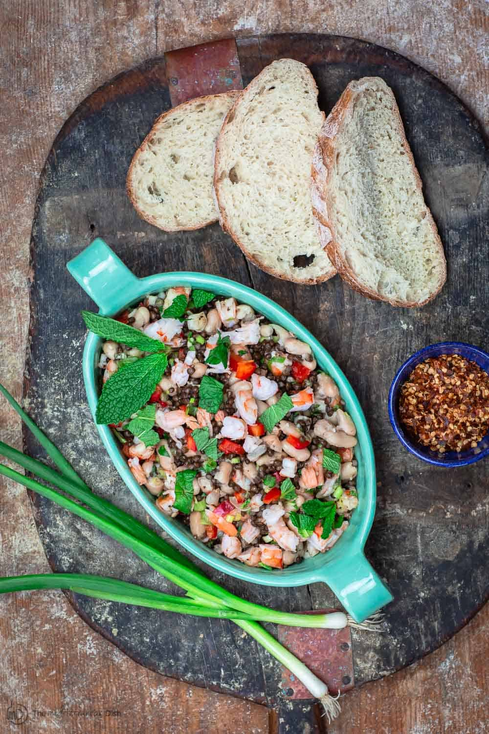 White bean salad in a serving bowl. Served with crusty bread, and a side of red pepper flakes
