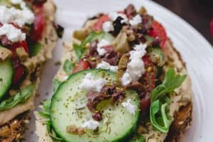 Mediterranean-Style Breakfast Toast with hummus, arugula, cucumbers, tomatoes, olives, a sprinkle of za'atar and feta cheese
