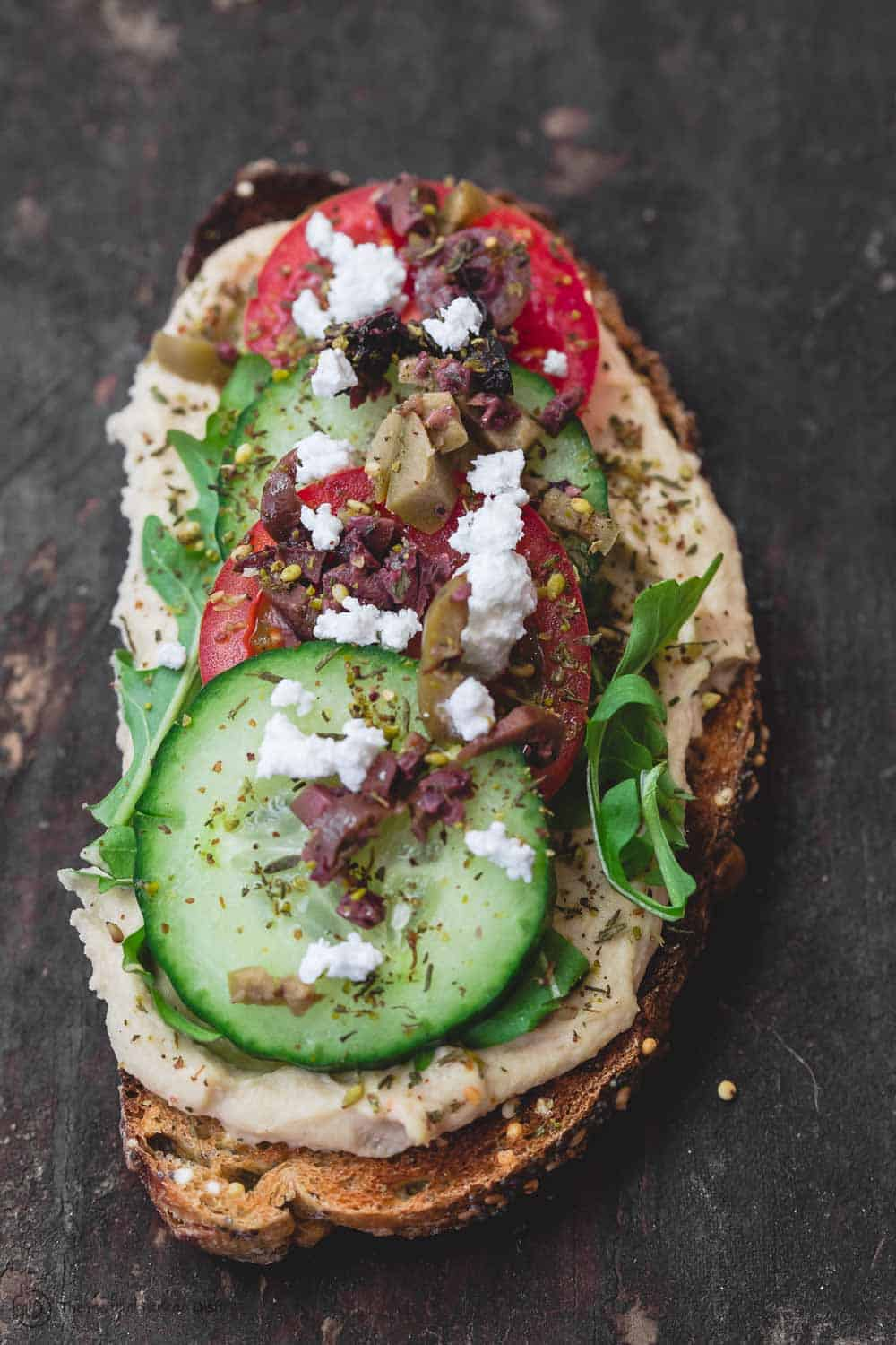 One slice of Mediterranean-style breakfast toast loaded with hummus, arugula, cucumbers, tomatoes, olives, a sprinkle of za'atar and feta cheese