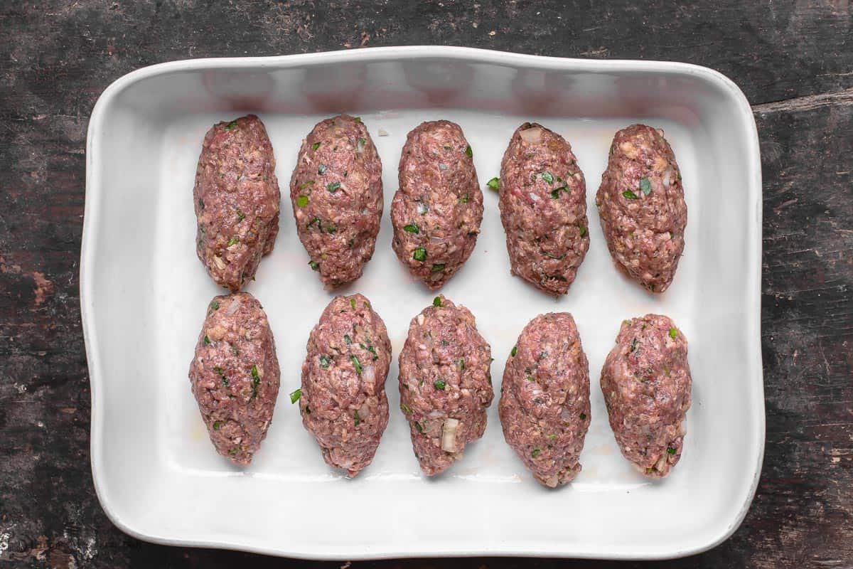 Meat mixture formed into elongated meatballs the shape of a football. Arranged in a baking dish