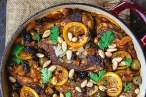 Moroccan chicken with lemons, olives, and dried fruit. Garnished with fresh cilantro and toasted almonds and served with couscous and more olives to the side