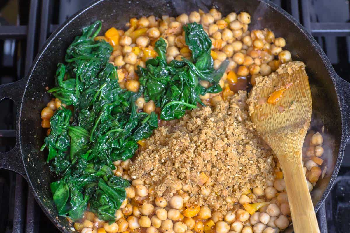 Spinach and almond and bread paste added to chickpeas to make chickpea stew