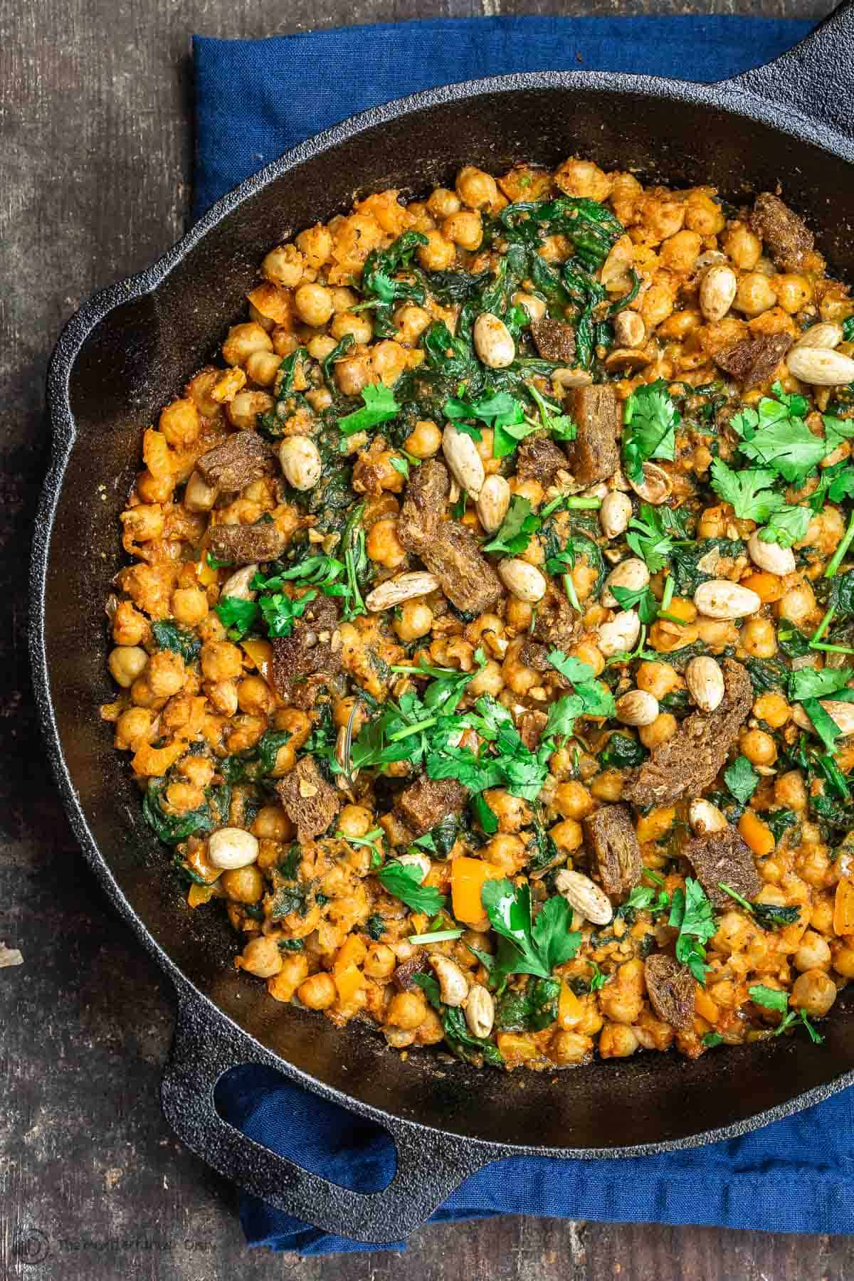 Finished skillet of Chickpea Stew with a garnish of almonds and cilantro
