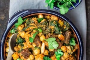 Chickpea Stew Garnished with Cilantro. More cilantro in a small bowl on the side