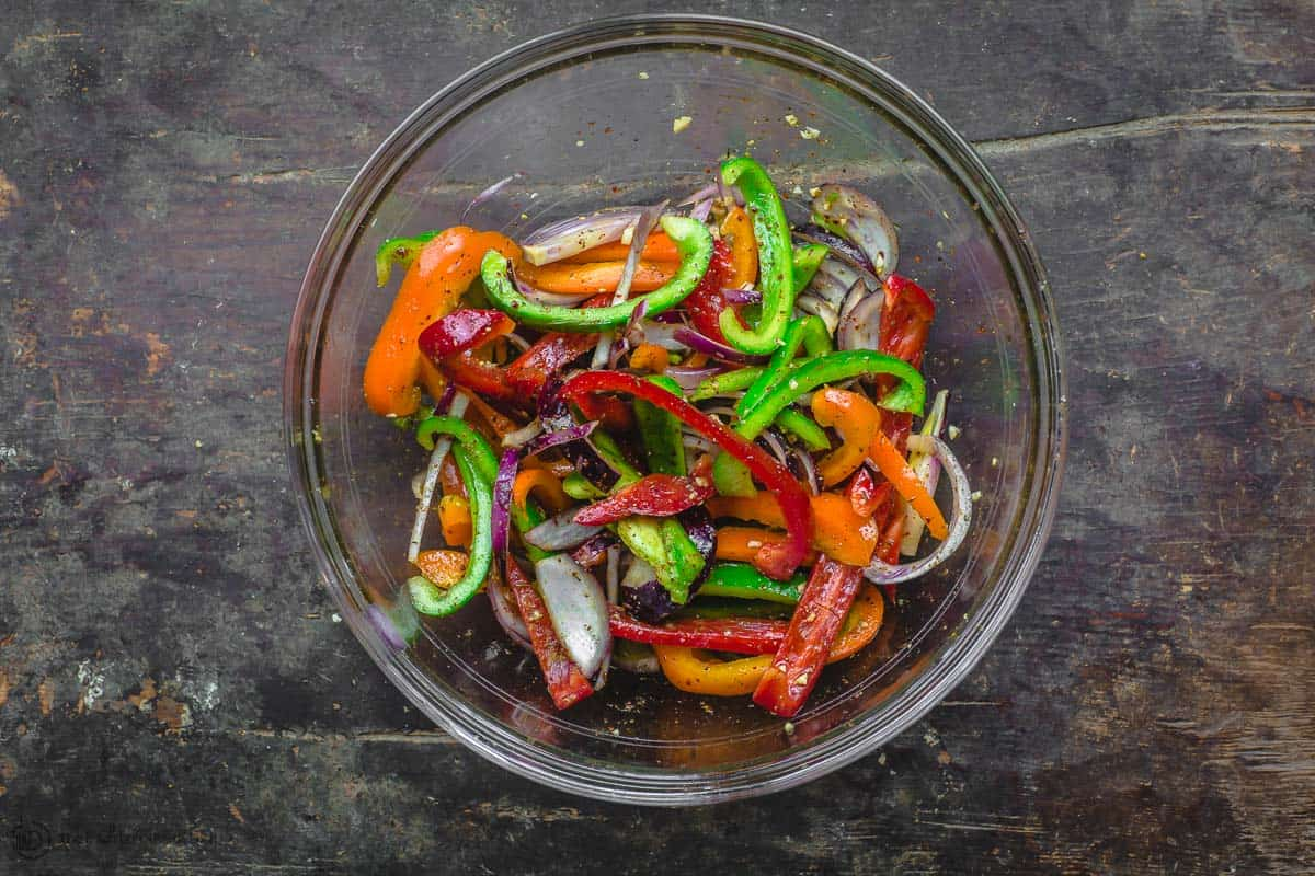 Thinly sliced bell peppers and red onions tossed in olive oil and spices in large mixing bowl