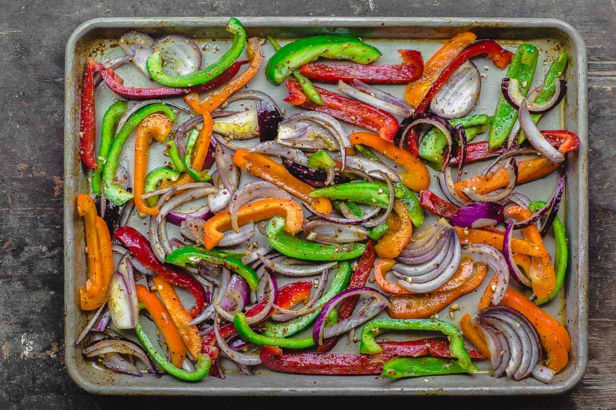 Bell peppers and red onion slices spread on sheet pan to bake