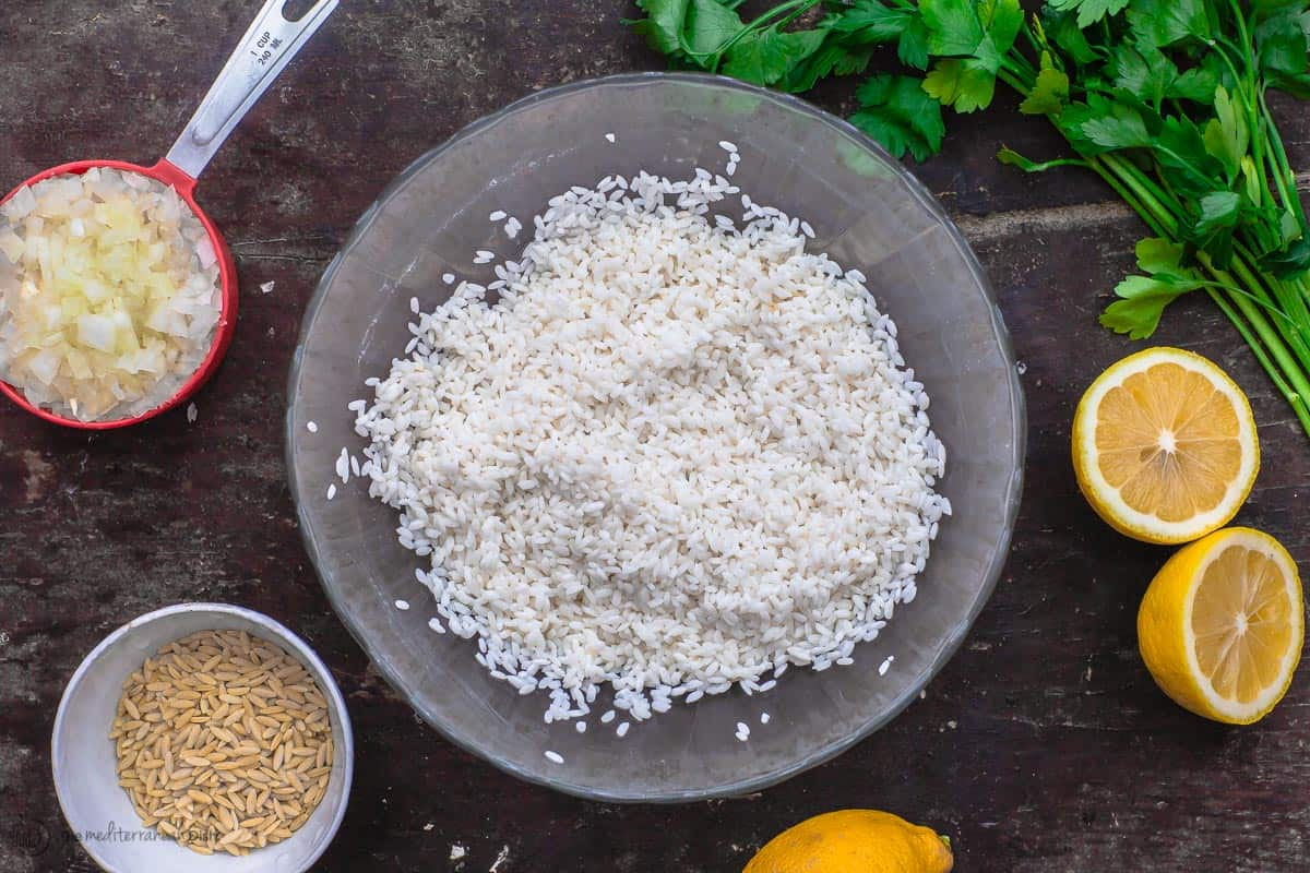 Some Greek lemon rice ingredients. Rice, orzo, fresh lemon, chopped onions and fresh parsley